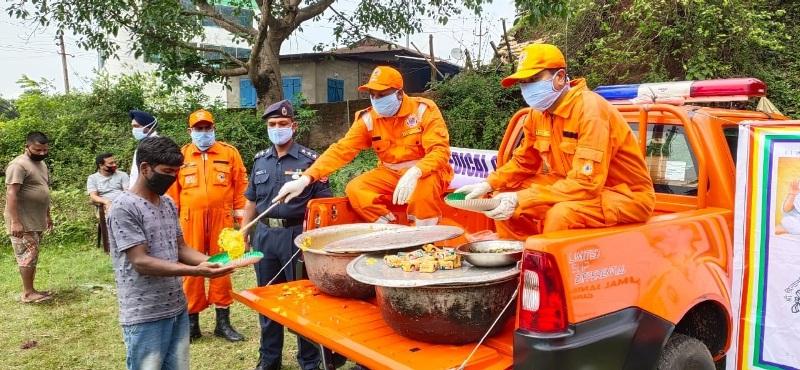 National Disaster Response Force (NDRF) 1st Bn Guwahati distributes food and masks